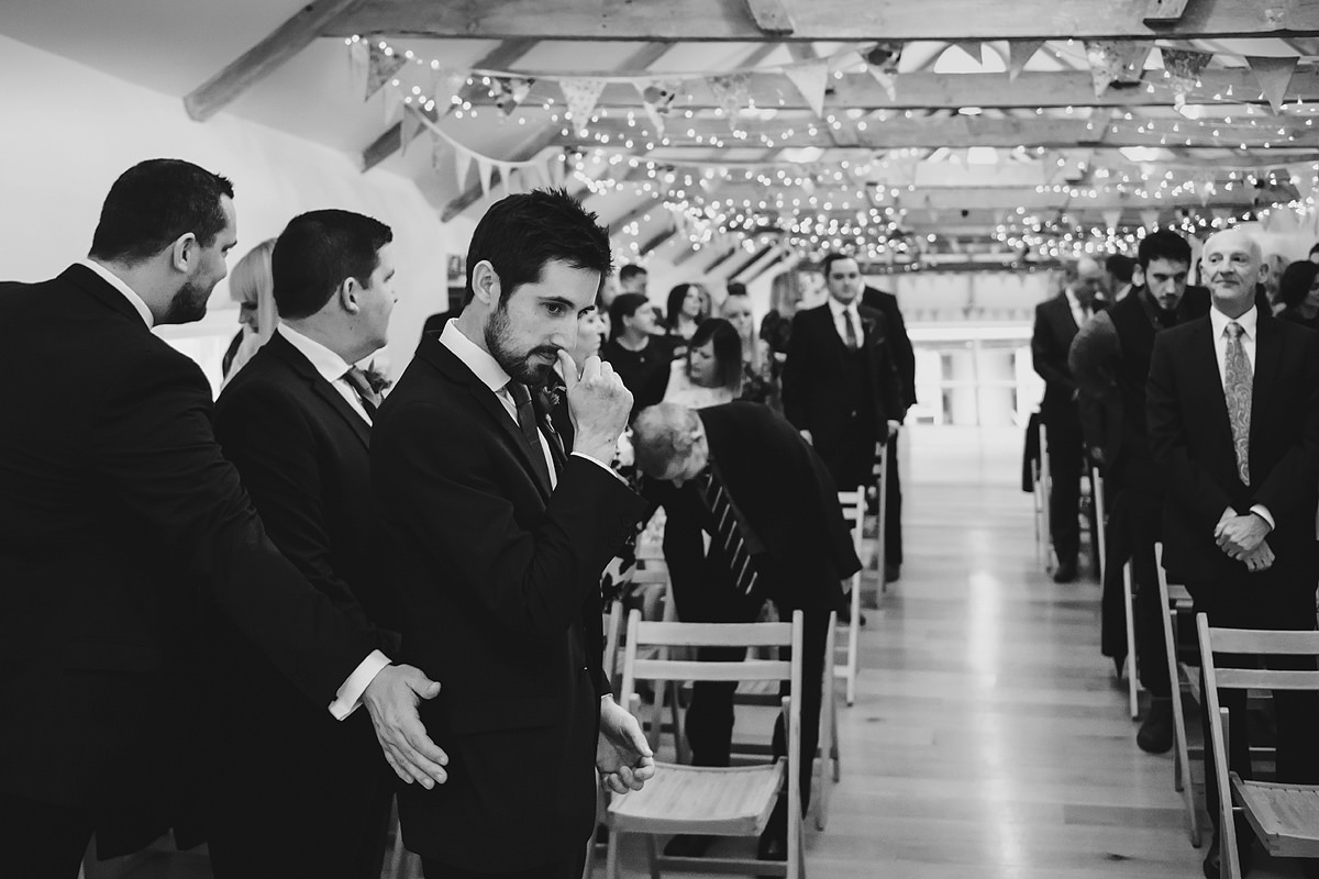 Groom waiting for bride in wedding barn