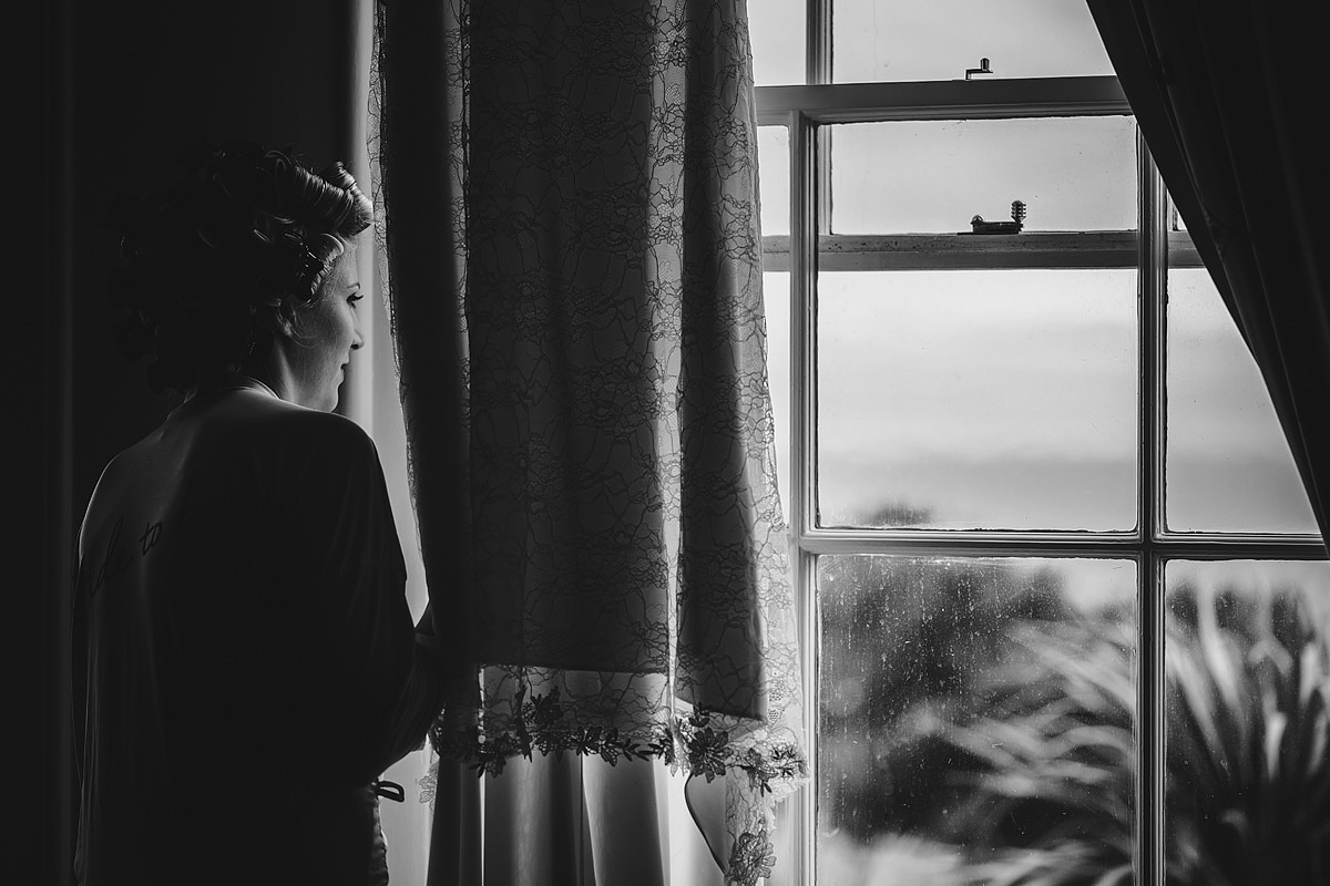 Bride looking out of window at Tregenna Castle