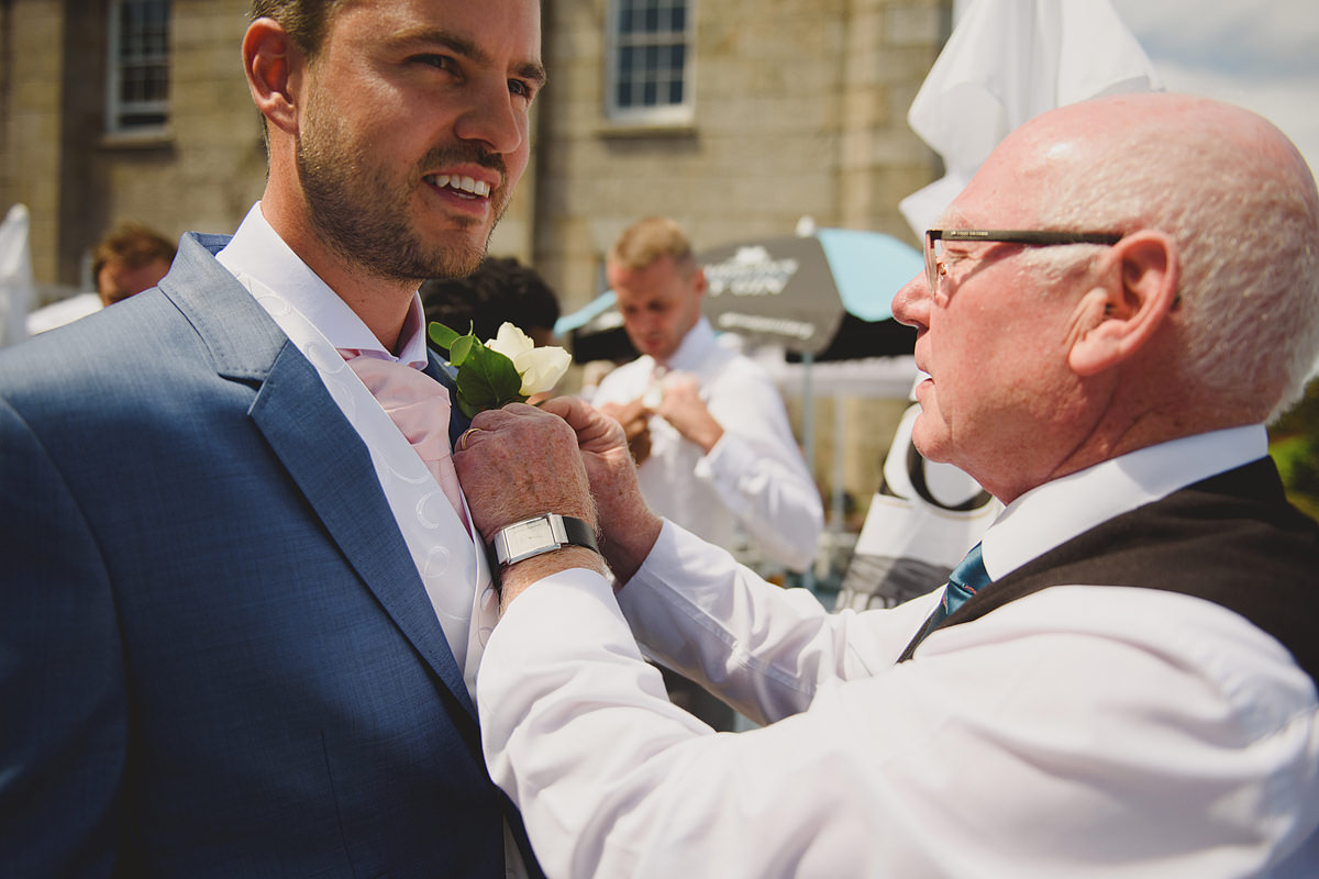 Groom putting on button hole at a Tregenna wedding