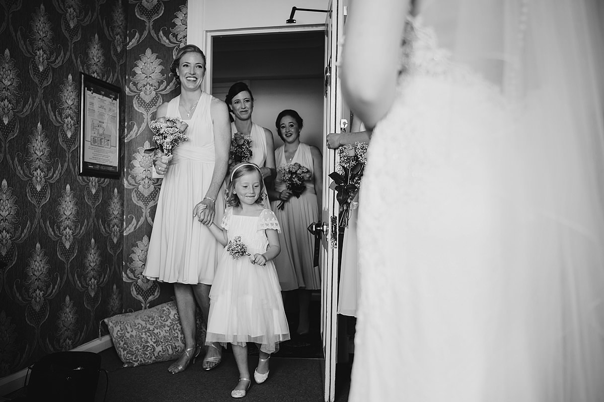 Bridesmaids seeing bride in wedding dress